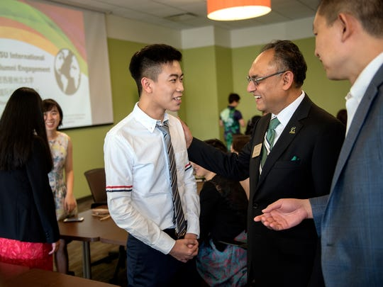 Michigan State University student, Chen Gong, from China, meets with Broad College of Business Dean Sanjay Gupta, center, during a lunch for Chinese students graduating from the business college on Saturday, May 5, 2018, at Brody Hall on the MSU campus in East Lansing. Associate professor John Jiang looks on at right.