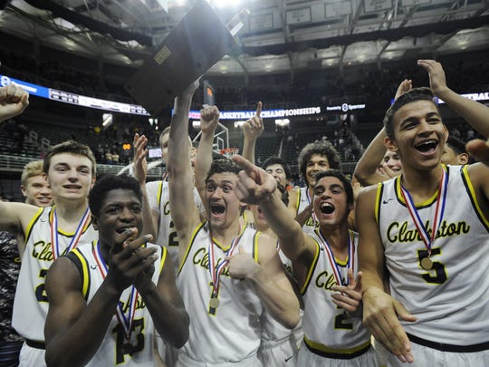 Clarkston players celebrate after defeating Grand Rapids Christian, 75-69, in the MHSAA Class A boys basketball final at the Breslin Center on Saturday, March 25, 2017.
