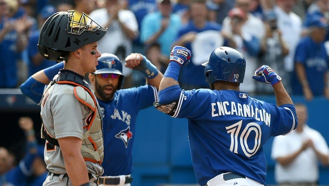 Toronto Blue Jays designated hitter Edwin Encarnacion (10) is greeted at home plate by right fielder Jose Bautista (19) after hitting a grand slam home run against the Detroit Tigers in the seventh inning at Rogers Centre. Looking on is Tigers catcher James McCann (34).