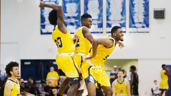 Lehigh Senior High School basketball players celebrate beating Golden Gate in the Class 7A region quarterfinal Thursday at Lehigh Senior High School. Lehigh beat Golden Gate 49-47.