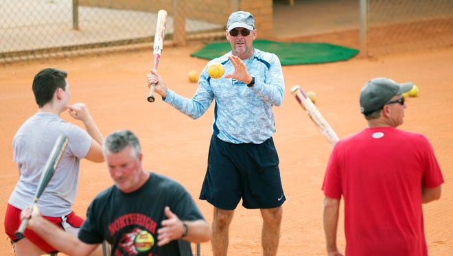 North Fort Myers High School softball coach Jeff Miner, center, leads practice Wednesday at North Fort Myers.