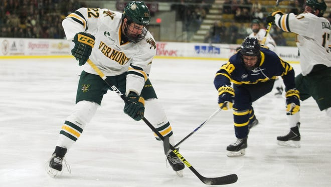 Catamounts forward Brady Shaw (22) play the puck during the men's hockey game between the Merrimack Warriors and the Vermont Catamounts at Gutterson Fieldhouse earlier this season.