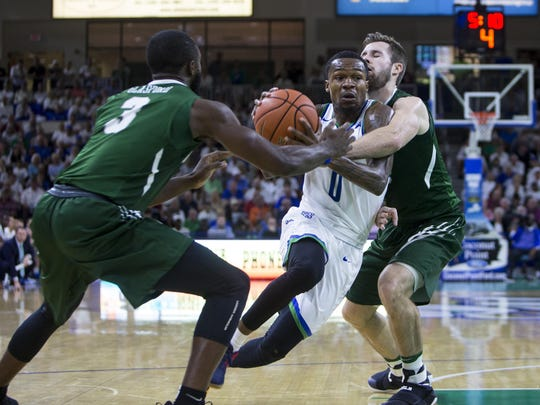 Florida Gulf Coast University junior, Brandon Goodwin, #0, goes for a lay-up against the Stetson defense during the game against Stetson University on Thursday at Alico Arena in Estero.