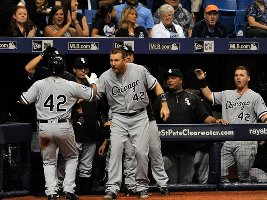 Chicago White Sox's Brett Lawrie, center, and teammates greet Jimmy Rollins, left, at the dugout after Rollins scored on Melky Cabrera's single off Tampa Bay Rays reliever Alex Colome during the ninth inning of a baseball game Friday, April 15, 2016, in St. Petersburg, Fla. (AP Photo/Steve Nesius)