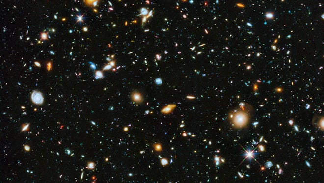 This handout composite image provided by NASA shows the visible and near infrared light spectrum collected from NASA's Hubble Space Telescope over a nine-year period. The Hubble Space Telescope has captured our cosmos at its most colorful. A new NASA panorama looking deep and far into the universe for the first time includes ultraviolet light, which is normally not visible to the human eye. It shows up in the photo as bright baby blue with spinning galaxies, which are about 5 to 10 billion years old, not too old or young in cosmic terms. The photo was taken over 841 orbits of the telescope and shows about 10,000 multi-colored galaxies.