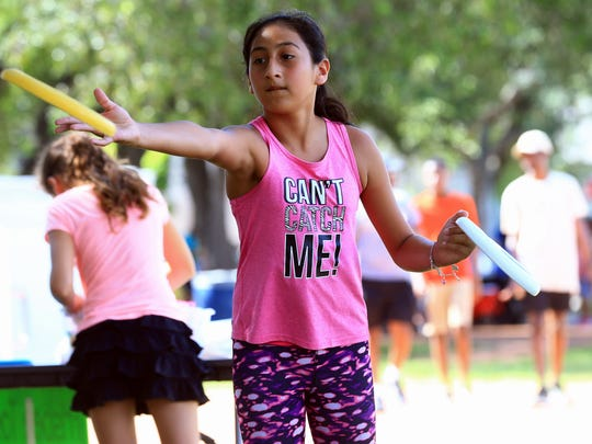 Aliza Sanchez throws a frisbee as she plays games during the Get Your Play On Festival on Saturday, July 15, 2017, at Heritage Park in Corpus Christi.