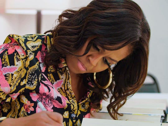 """Former first lady Michelle Obama signs a copy of her autobiography in """"Becoming."""""""