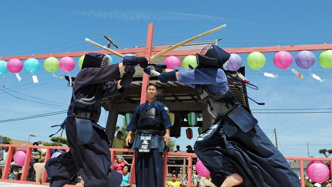 "Members of Salinas Kendo Dojo look for points during their demonstration at Sunday's annual Obon Festival at the Buddhist Temple of Salinas. Obon is one of the summer festivals observed throughout Japan. It is usually held in the middle of August when Buddhists pay respect to their ancestors, including family members, relatives and friends. The event culminates in the ""Bon-Odori"" where participants meet new friends and join together in a traditional dance of joy."