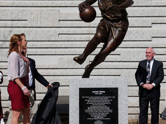 Jackie Stiles, left, sees her statue for the first time as it is unveiled outside JQH Arena in Springfield on Feb. 12, 2017.