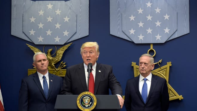 President Donald Trump, center, flanked by Vice President Mike Pence, left, and Defense Secretary James Mattis, right, speaks during an event at the Pentagon in Washington, Friday, Jan. 27, 2017.