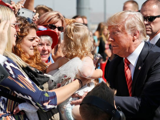 President Donald Trump tries to hold a baby as he greets