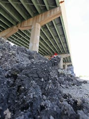 Contaminated soil excavated during emergency bridge repairs rests in a pile, waiting to be taken away for disposal, Friday, June 20, 2014.