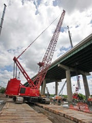 A crane lowers a 150 foot piece of caging through a six by six foot hole in the southbound lane of the I-495 bridge over the Christina River last month.