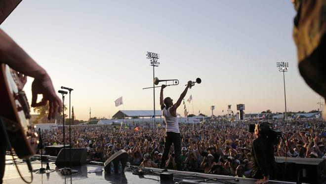 Trombone Shorty reacts to the crowd as he closes out the final set of the 2015 New Orleans Jazz and Heritage Festival in New Orleans, Sunday, May 3, 2015. (AP Photo/Gerald Herbert)