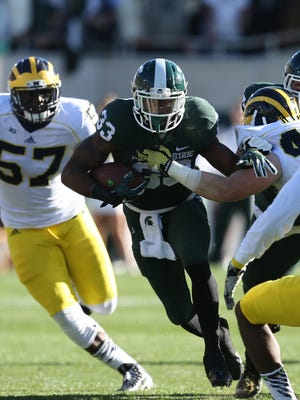 Michigan State's Jeremy Langford runs by Michigan defenders during the second quarter on Oct. 25, 2014, at Spartan Stadium.