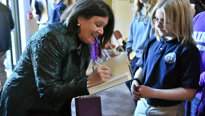 """Oscar-nominated actress Mary Badham signs the book """"To Kill a Mockingbird"""" for Episcopal School student Bruin Webster. Badham visited the school on April 30 to share her experience filming the 1963 movie of the same name."""
