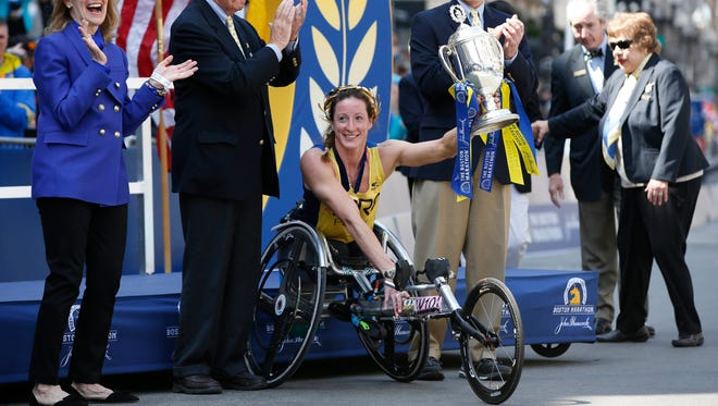 Tatyana McFadden of the United States holds the trophy after winning the women's wheel chair division of the 120th Boston Marathon.