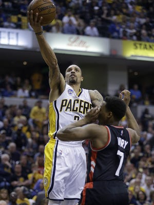 Indiana Pacers guard George Hill (3) lays in a shot over Toronto Raptors guard Kyle Lowry (7) in the first half of their Eastern Conference first round playoff game Saturday at Bankers Life Fieldhouse.