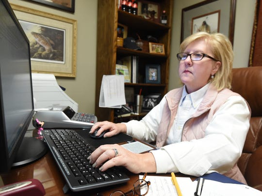 Marion County Sheriff Joan Vickers taps out an email to her staff Friday. Vickers said working in the office her husband occupied prior to his death last year gives her strength.