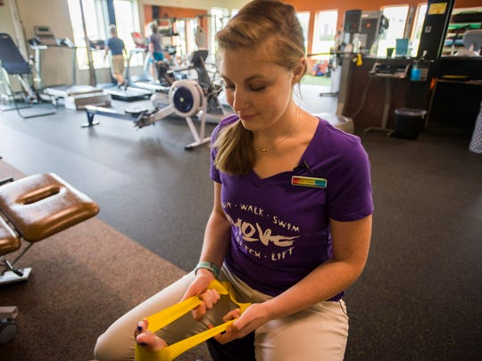 Caitlin Thornton of RehabGYM helps a client with physical therapy at their new facility at  Kismet Place in Williston.
