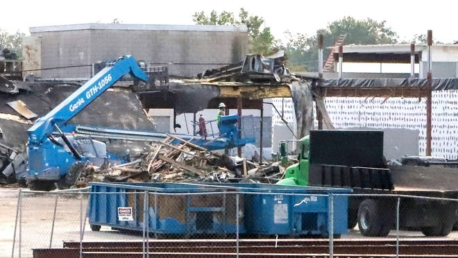 Workers use lifts to remove the debris on the Wheeler Avenue side of the Phoneix Village Mall, Thursday, Oct. 9, as part of the 100,000 square feet demolition and renovation featuring a planned green space with walking trails and other aminities.