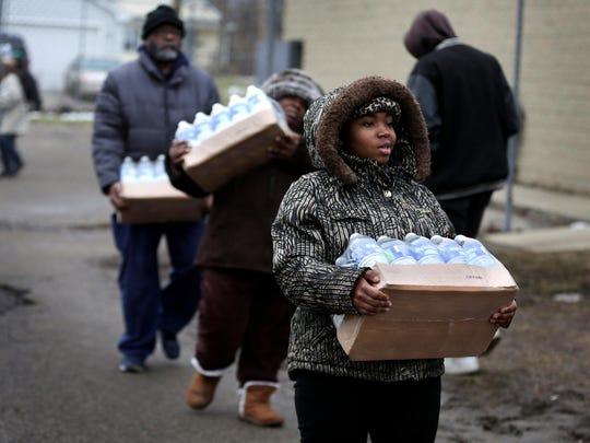 Flint residents pick up cases of bottled water at Flint Fire Station 3 Jan. in Flint.