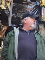 Bob Paradise, 58, stands amid the rubble of his home