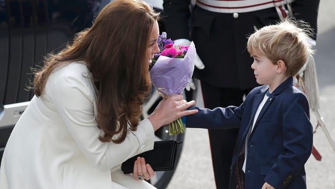 Duchess Kate of Cambridge accepts bouquet from Zac Barker, child actor on 'Downton Abbey' during visit to Ealing Studios set in London on March 12.