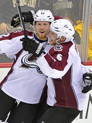 Colorado Avalanche defenseman Erik Johnson (6) congraulates Colorado Avalanche left wing Gabriel Landeskog (92) on his game winnging goal during the overtime period of an NHL hockey game against the Pittsburgh Penguins on Monday, Oct. 17, 2016, in Pittsburgh. The Avalanche defeated the Penguins 4-3.