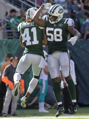 New York Jets' Buster Skrine (41) and Darron Lee (58) celebrate after Skrine sacked Miami Dolphins quarterback Jay Cutler during the second half of an NFL football game Sunday, Sept. 24, 2017, in East Rutherford, N.J. (AP Photo/Bill Kostroun)