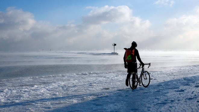 A bike commuter walks on an ice-covered path near Lake Michigan, Monday, Jan. 5, 2015, in Chicago. Forecasters expect more snow and freezing temperatures this week in northern Illinois.