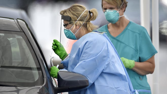 Medical personnel get samples during drive-up COVID-19 testing at Good Shepherd Baptist Church in Augusta, Ga., Friday morning May 22, 2020.