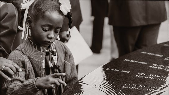 A child touches the water flowing over the Civil Rights