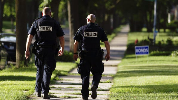 Milwaukee police patrol the neighborhood near the scene where a stolen car chase ended on June 18. A state Supreme Court ruling on Thursday affirmed a state law barring municipalities from imposing residency rules on their employees.
