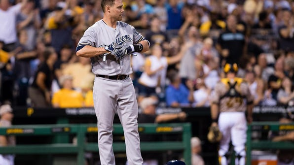 Brewers infielder Jake Elmore takes off his batting gloves after striking out in the sixth inning during the game against the Pittsburgh Pirates at PNC Park on July 21, 2016.