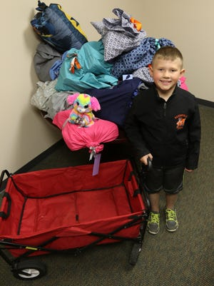 Sam Heiman, 8, poses with 28 bags of donations he collected at a birthday party as opposed to presents, in Marshfield News-Herald office May 9, 2016. Heiman's eight friends gave donations instead of presents.