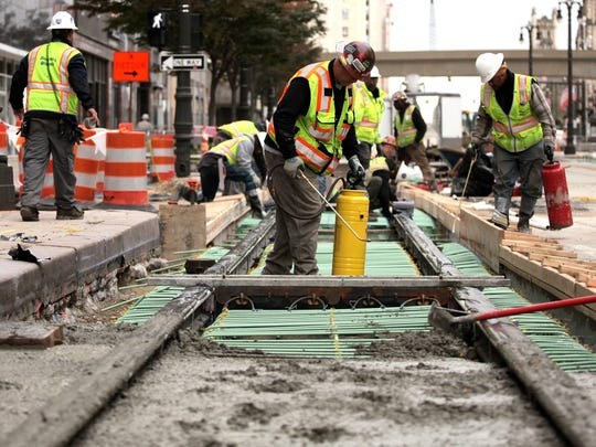 Construction workers building the M-1 Rail line on Woodward Avenue in mid-2015. M-1 officials and Quicken Loans executives will announce the name for the line on Tuesday Nov. 24, 2015.