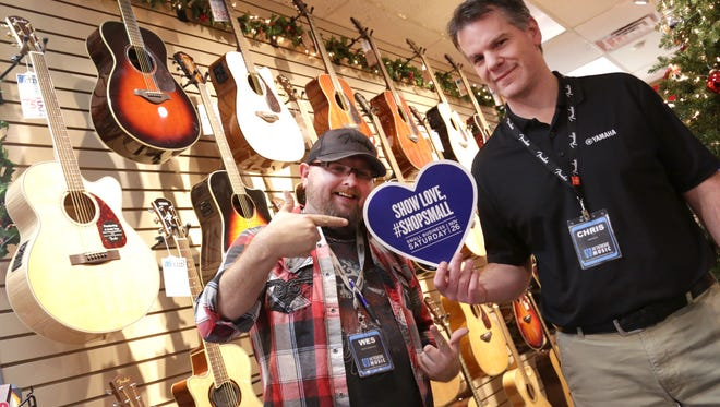 Wes Porter and Chris Stecker of Metronome Music hold a sign in support of Small Business Saturday, in which they are participating with 92 other businesses in the county.