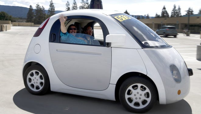 A Sacramento resident tries out a Google self-driving car prototype.