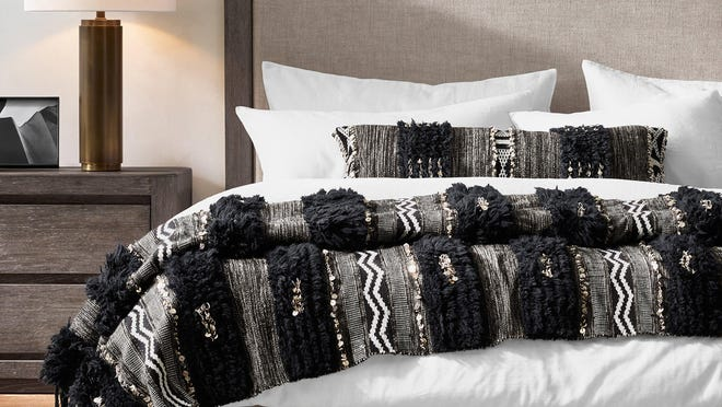 A wool and cotton Moroccan wedding blanket is embellished with fringe and metallic sequins.