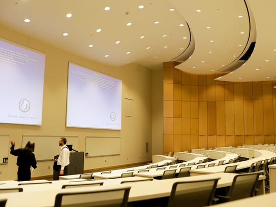 People tour a lecture hall for medical students at