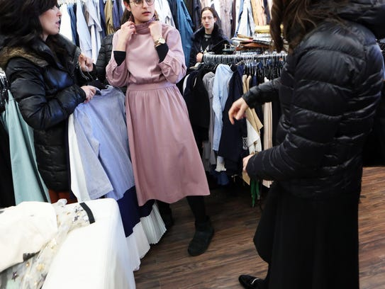 A young Orthodox Jewish woman tries on a dress while