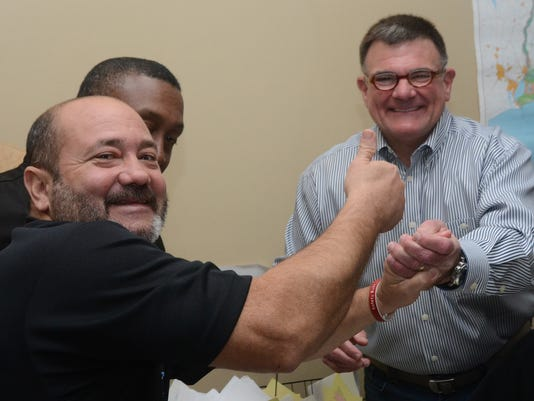 ANI Phillip Terrell Vince Giambrone Jr. (left, front) and Leroy Williams (back, left) congratulate Phillip Terrell (far right) Saturday, Dec. 6, 2014 on his victory in the ninth judicial district court race for district attorney.-Melinda Martinez/mmartinez