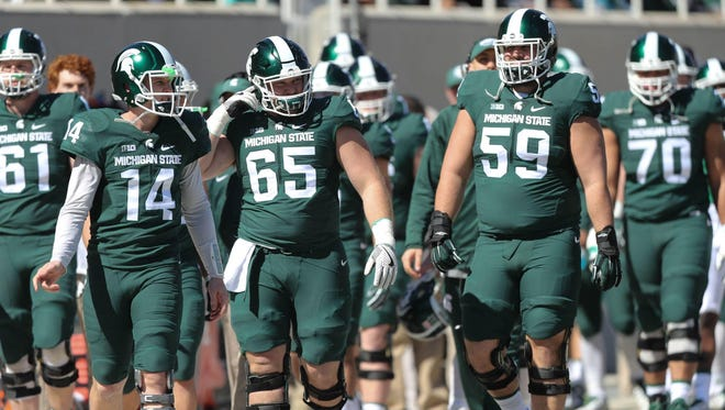 Quarterback Brian Lewerke, from left, and offensive linemen Brian Allen and David Beedle take the field for the spring game April 1.