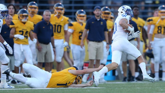 St. Xavier wide receiver Jared Kreimer (10) returns a punt for a touchdown in the first quarter during the high school football game between the St. Xavier Bombers and Moeller Crusaders, Friday, Sept. 22, 2017, at Roettger Stadium in Lockland, Ohio.