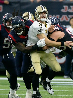 New Orleans Saints quarterback Drew Brees (9) throws a pass before being hit by Houston Texans' J.J. Watt (99) and Jadeveon Clowney, left, during the third quarter of an NFL football game Sunday in Houston.
