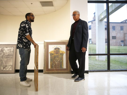 """Khalil Kinsey and his father, Bernard, who founded """"The Kinsey Collection,"""" work to help display the over 100 pieces of African-American history, artifacts, documents, and artwork at the Foster-Tanner Fine Arts Center on FAMU's campus Thursday."""