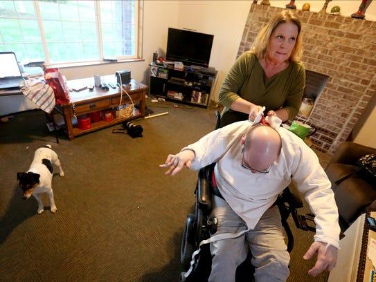 Julie Miller helps her son, Chris Barrilleaux, 27,
