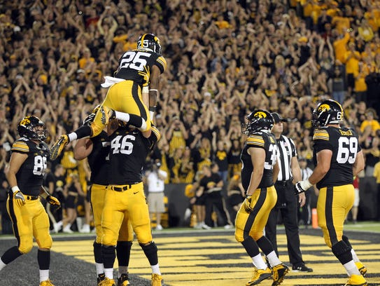 Iowa's George Kittle (46) lifts running back Akrum