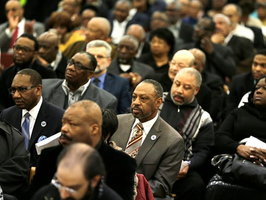 People listen as pastors with the Detroit Water Equity